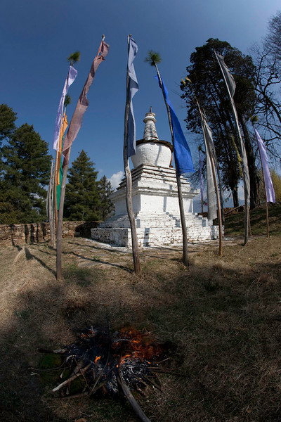 A ceremonial fire as new prayer flags are raised at the chorten