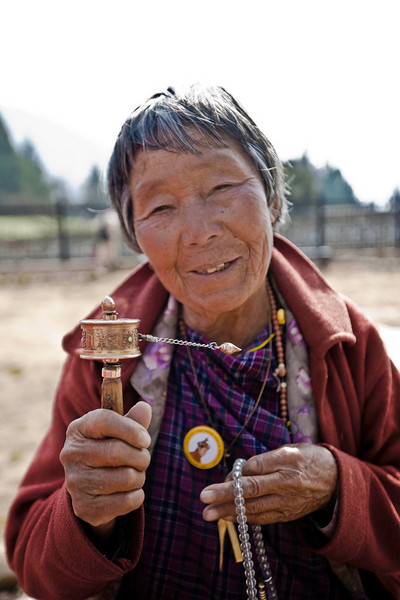 Each revolution of the prayer wheel repeats a prayer as she walks around the central chorten