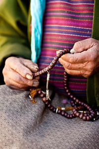 Counting the 108 beads to accompany 108 prayers.  Old hands, old beads, an act oft repeated in Bhutan