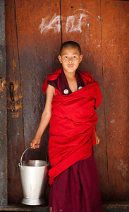 A young monk doing chores in Wangdue