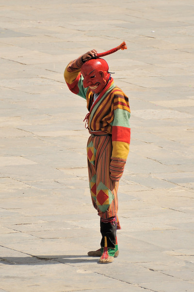 Atsara or clown explains the meaning of mask dances to spectators, entertains them when dancers are in the changing room, and help control the crowd.  Atsara is derived from the Sanskrit word Acharya (holy teacher) or dubthop in Dzongkha. According to religious history, about 84 dubthops (Mahasiddhas), who had extinguished all defilements and afflictions, roamed the universe to subdue evil thoughts by mocking worldly things.  Weirdly dressed, whimsical, vulgar and abusive in language, the dubthops used their wit, foolery, and drollery, together with their powers to uproot evil from the minds of mortals. <br /> Atsaras today represent these learned and saintly beings. Their apparent vulgarity arises out of their detachment from human feelings like embarrassment, hesitation, and reservation.