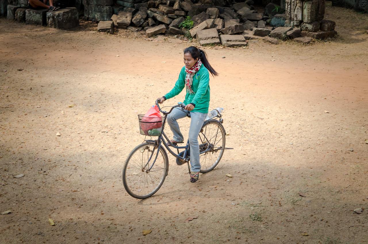 A local girl rides her bike through Angkor Thom.