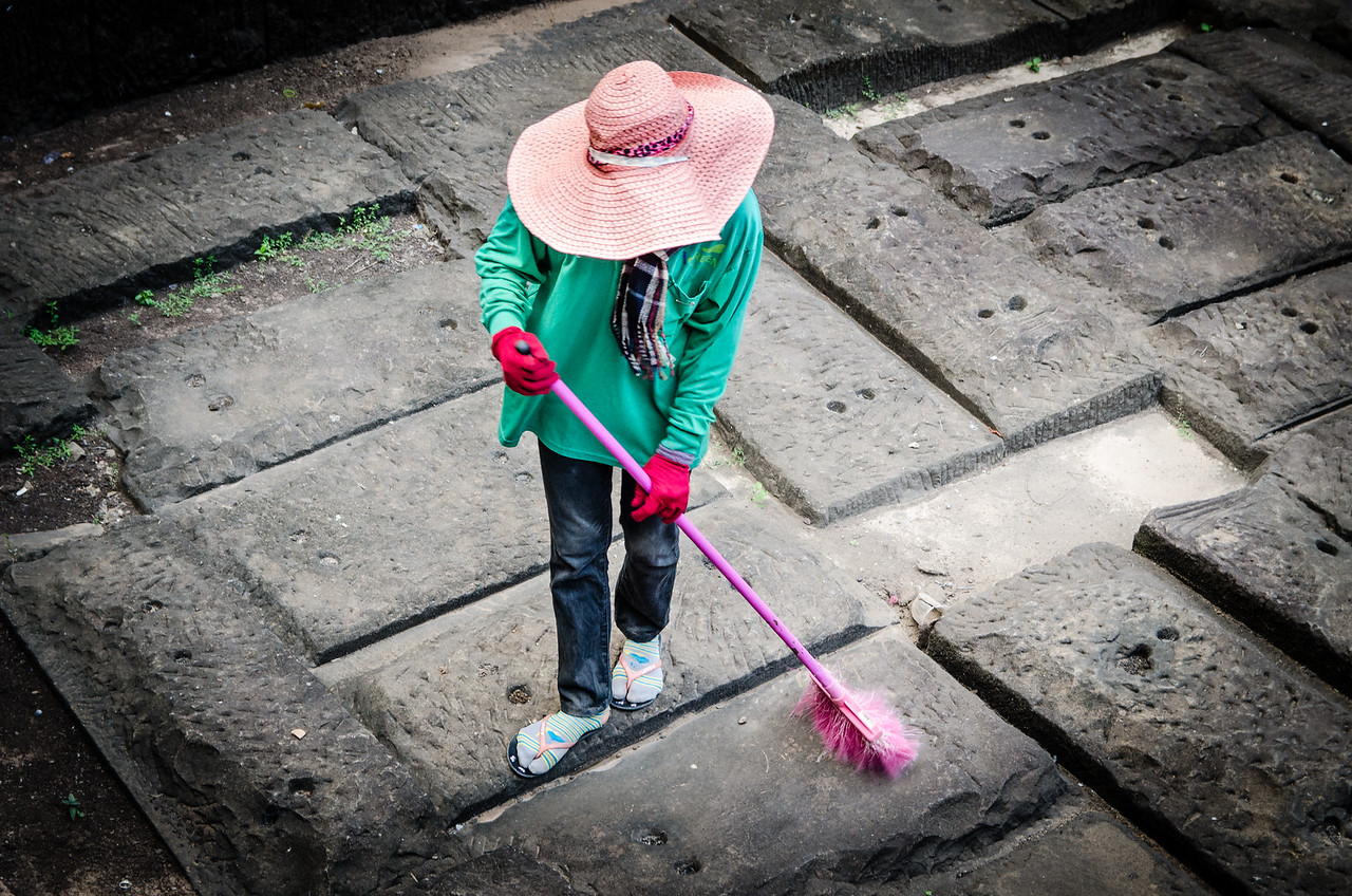 Woman sweeping up.