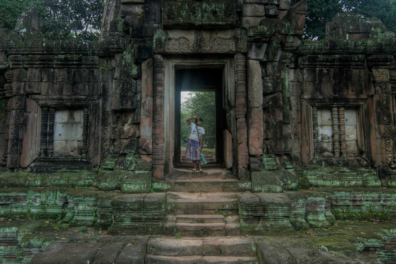 Girl waving in a doorway at the Angkor Wat ruins