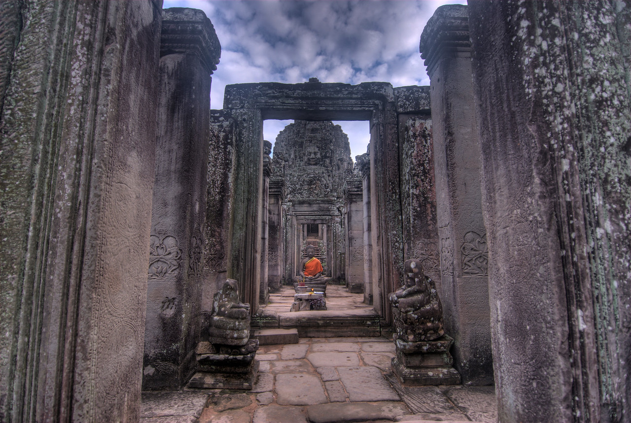 A buddha statue in the middle of a doorway and halls in Bayon Temple