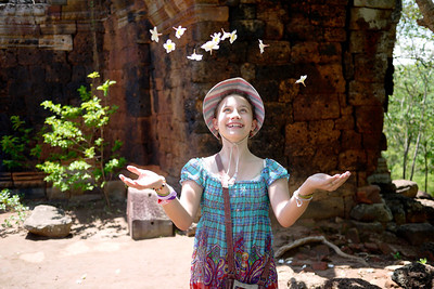Ana throws frangipani in the air after collecting the fallen blossoms from the floor of Wat Banan near Battambang, Cambodia