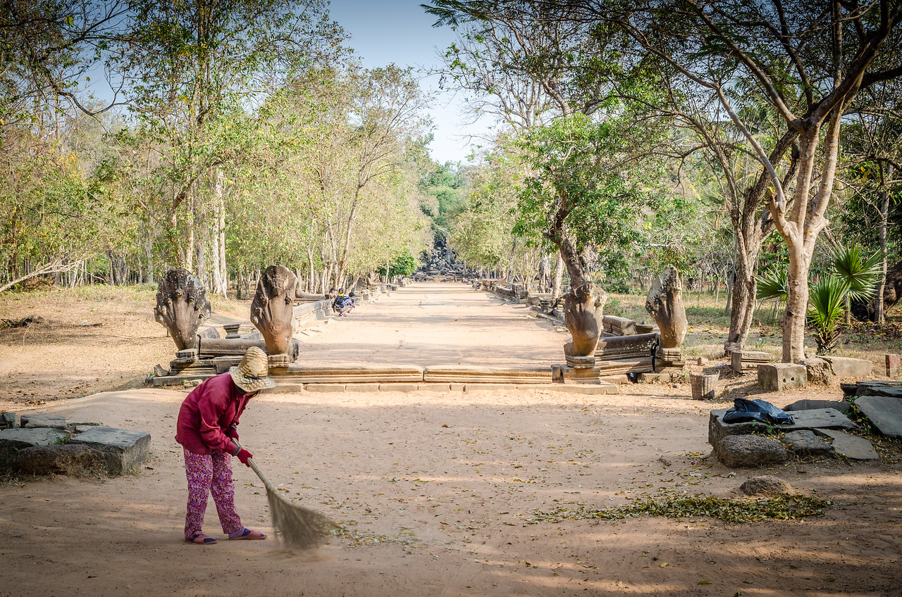 A woman sweeps leaves at the southern approach to Beng Mealea.