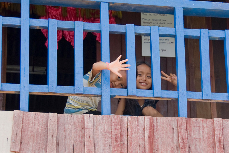 Two orphan kids waving at the camera in an orphanage in Phnom Penh, Cambodia