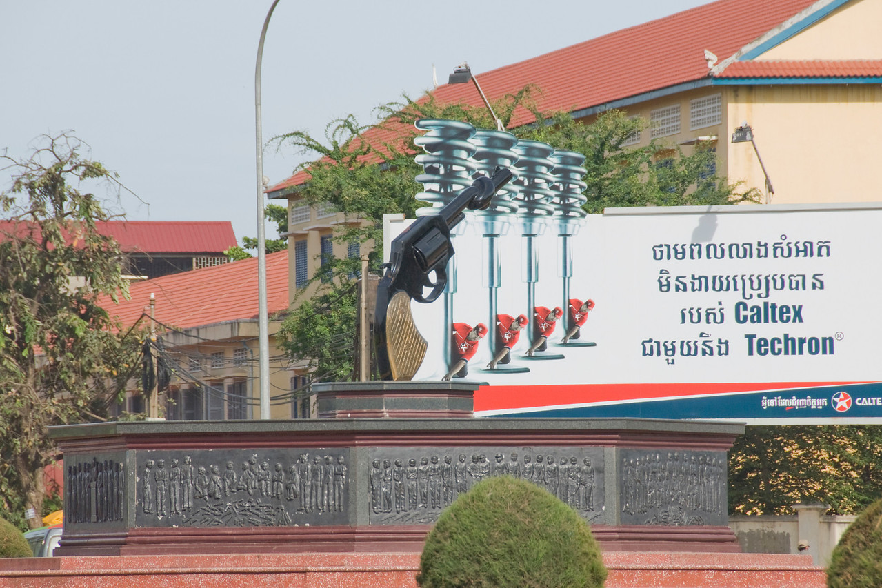 Knotted Handgun Sclupture near gas station sign in Phnom Penh, Cambodia
