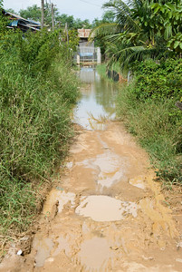 Muddy road leading to the entrance gate of an orphanage in Phnom Penh, Cambodia