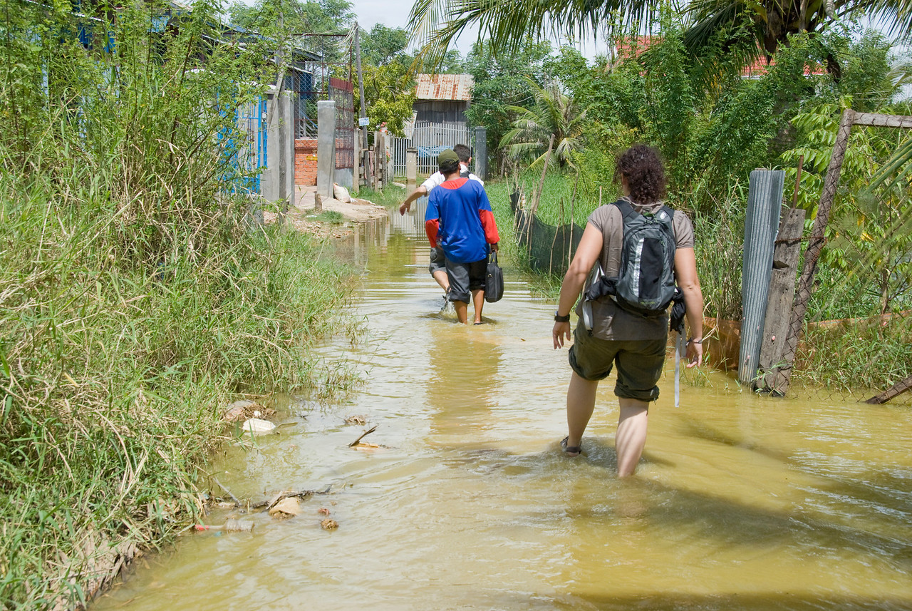 Walking through water-filled road going to orphanage in Phnom Penh, Cambodia