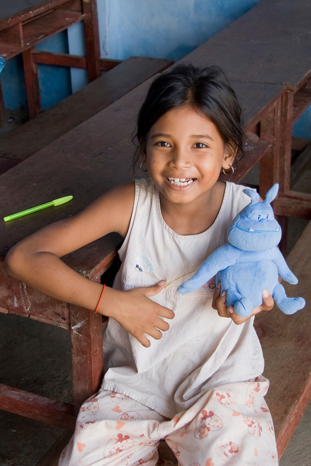 Orphan smiles to the camera while carrying Skull at an orphanage in Phnom Penh, Cambodia