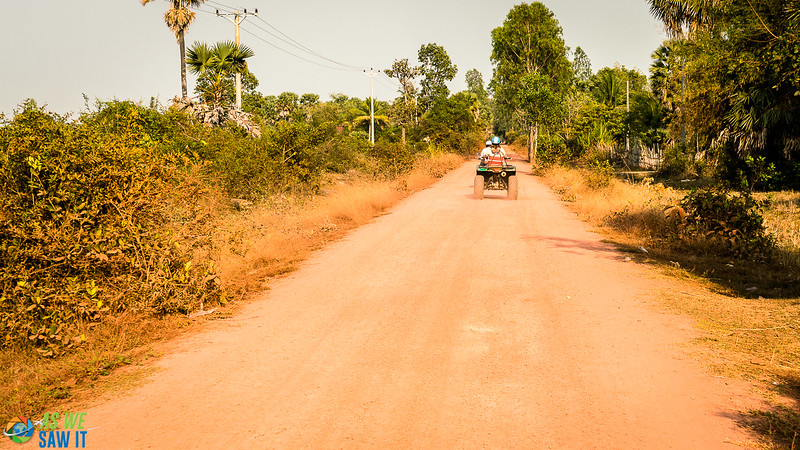 Quad bike rides down a red clay road in Siem Reap