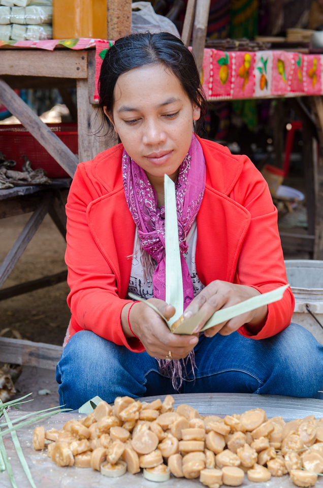 Woman packaging palm sugar for sale.