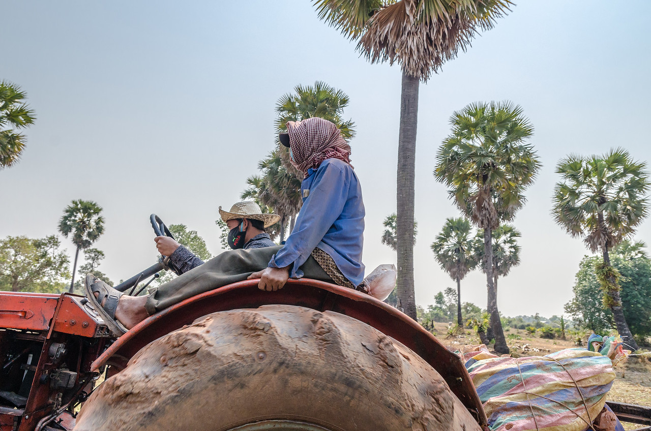 Men driving a tractor.