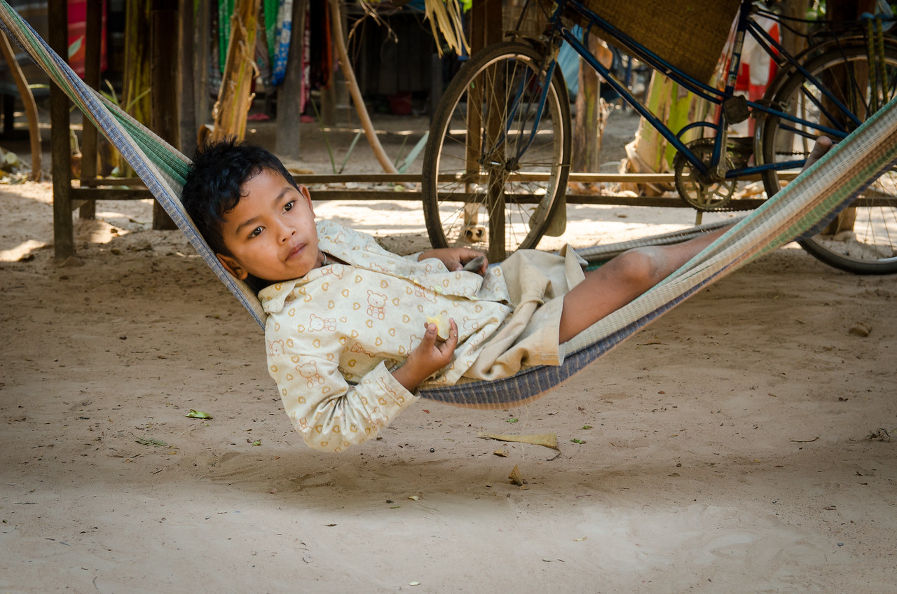 Boy relaxing on a hammock in the shade.