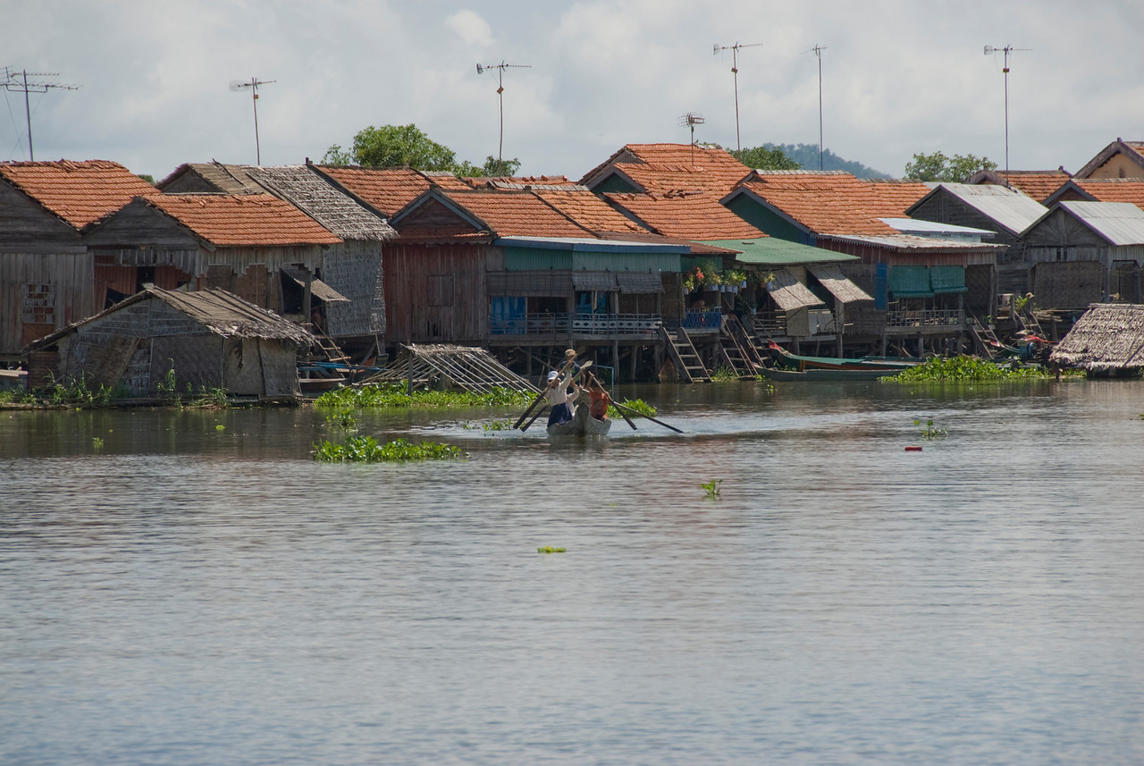 Children rowing a boat near a row of houses in Tonle Sap