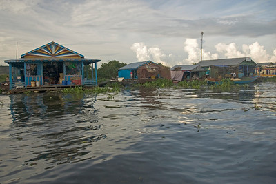 A shot of colorful floating houses in Tonle Sap at sunset