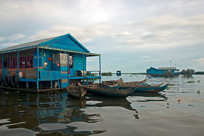 Boats parked outside a colorful floating school in Tonle Sap