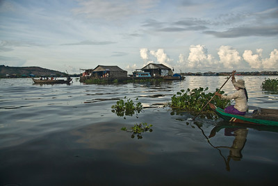 A woman rows a boat towards the floating houses in Tonle Sap