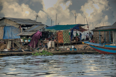 Dilapidated homes in Tonle Sap against beautiful sunset