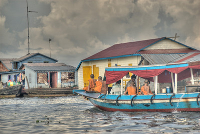 Monks riding on a boat in Tonle Sap, Cambodia
