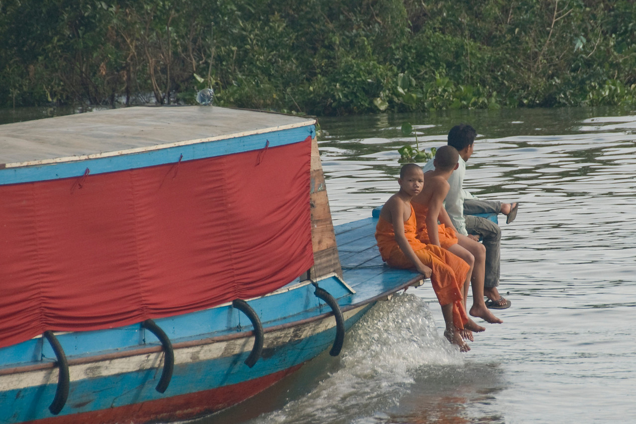 Monks resting on a boat in Tonle Sap, Cambodia