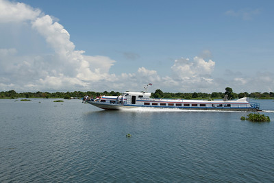 A transport boat carrying tourists cruising over Tonle Sap