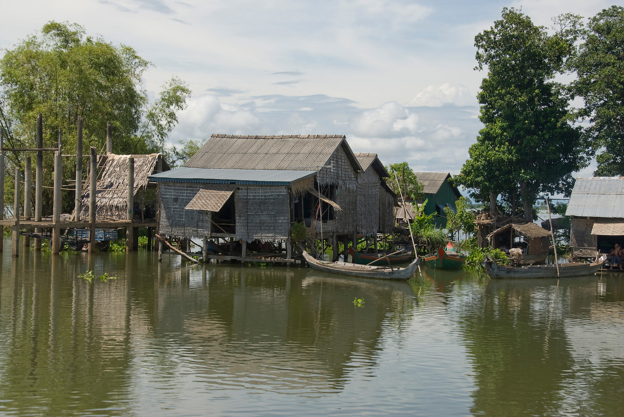Boats docked on the side of water huts in Tonle Sap, Cambodia