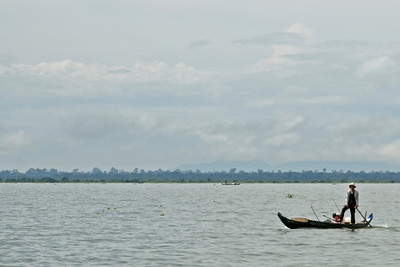 A man stands on a boat in Tonle Sap, Cambodia