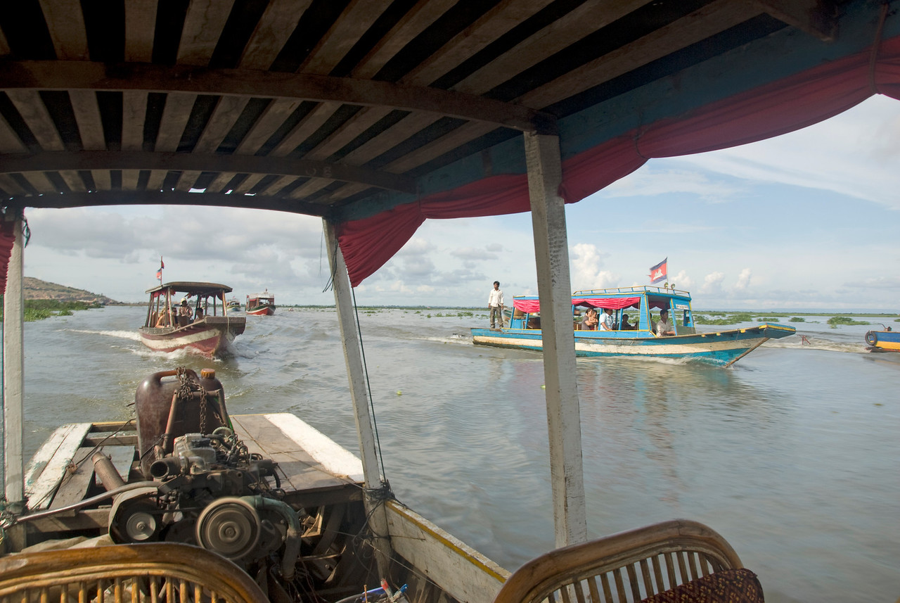 A shot of nearby tourist boats from a boat in Tonle Sap
