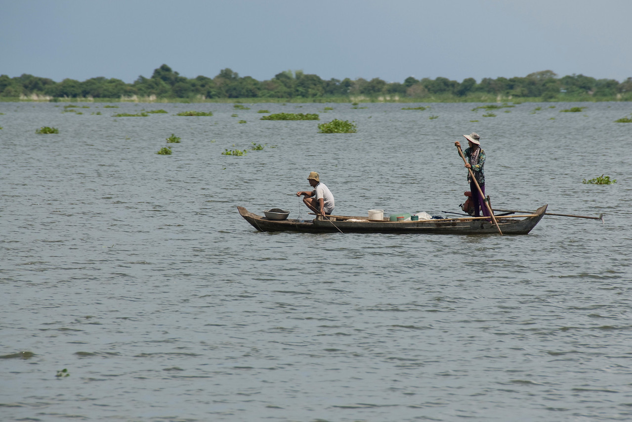 Two fishermen on a boat in Tonle Sap, Cambodia