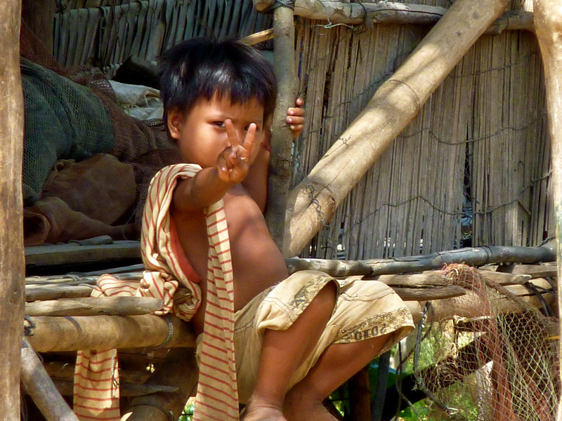 A little Cambodian boy giving the peace sign in the village of Kampung Phhluk