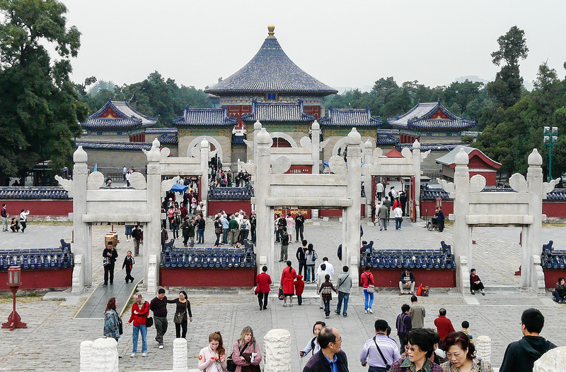 A series of white gates lead to buildings with blue tile roofs and red accents in Beijing.