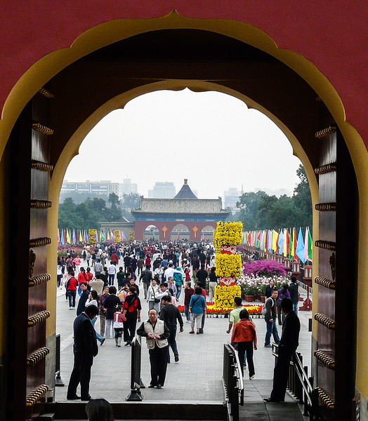 Looking through an arched wooden door highlighted in gold, you see a crowd of tourists walking among yellow flower displays at The Temple of Heaven.