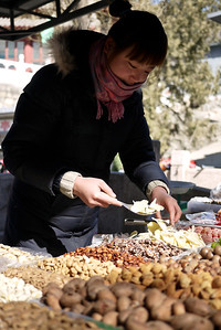 A vendor at the Great Wall serves up dried fruits and nuts in Beijing, China.