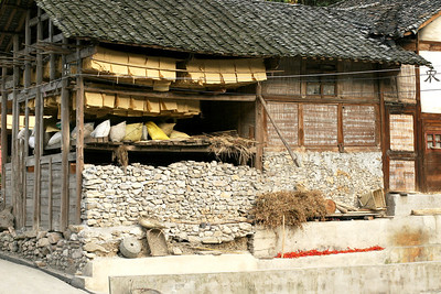 In Dazhai village, where we would spend the night.  The yellow sheets hanging from the rafters is newly-made paper drying.
