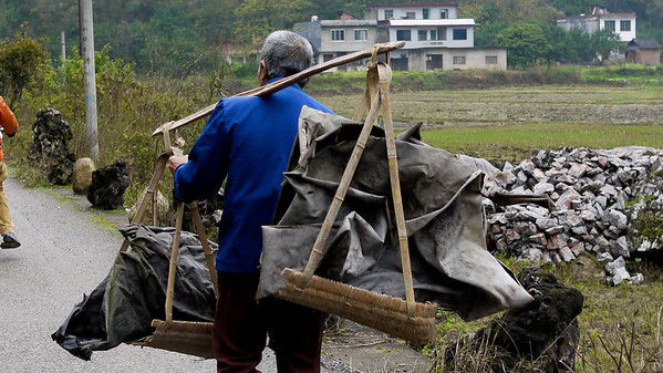 Workers shoulder heavy loads when working outside of Yangshuo, China.