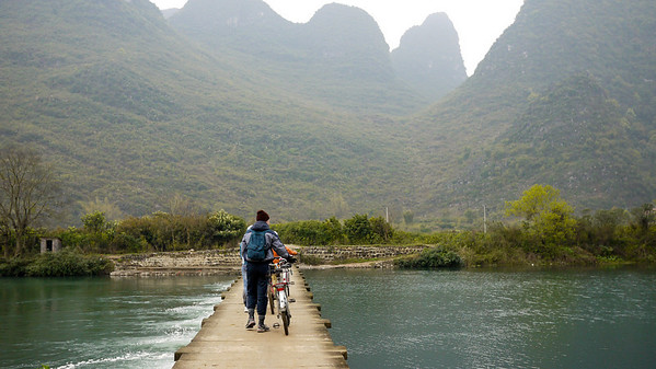 Walking out bikes across the thin bridges dotting the waters near Yangshuo, China.