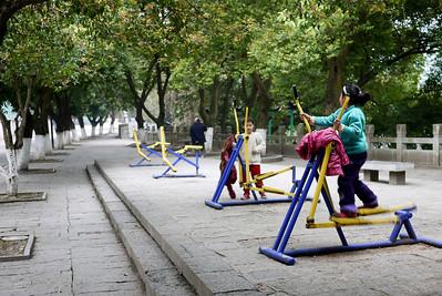 Children on park exercise equipment in Yangshuo, China.