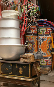 Goods for sale: rugs, pots, a stove and bridles for ponies.
