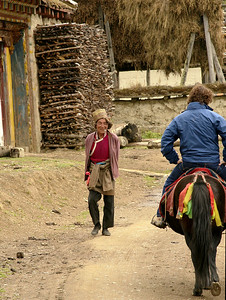 Clayton riding his pony up to a small monastery, passing a local guy en-route.