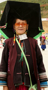 This lady is a member of the Yi minority, dressed in her festival clothes.  I don't believe the Elton John-like glasses are part of the traditional costume.