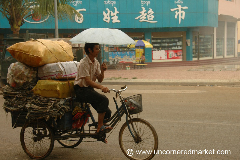 Man Cycling with an Umbrella - Xishuangbanna, China