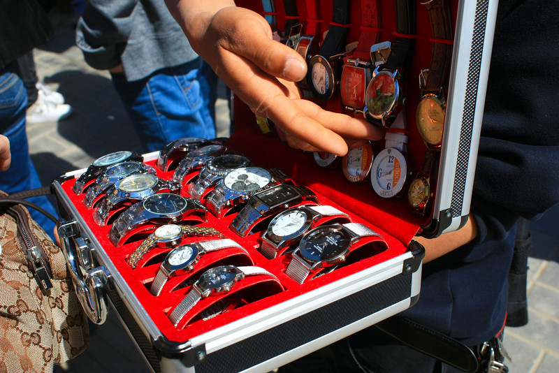 """A street vendor showing his assortment of """"Rolex"""" watches as he points to his top seller, the Chairman Mao watch."""