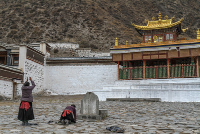 Pilgrims prostrating in front of Labrang monastery.