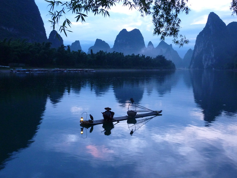 Fishermen using comorants to fish during the early morning hours before sunrise in Xingping, near Yangshuo in China.  I had to wake up at 4:30 in the morning and travel up the Li River by boat for thirty minutes for this shot.