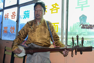 Tibetan man playing traditional guitar like instrument. Xiahe.