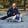 The entrance to the Temple of Heaven hosts several large park areas where Chinese come to exercise, practice martial arts, play games and spend time together. Here, father and son are stretching.
