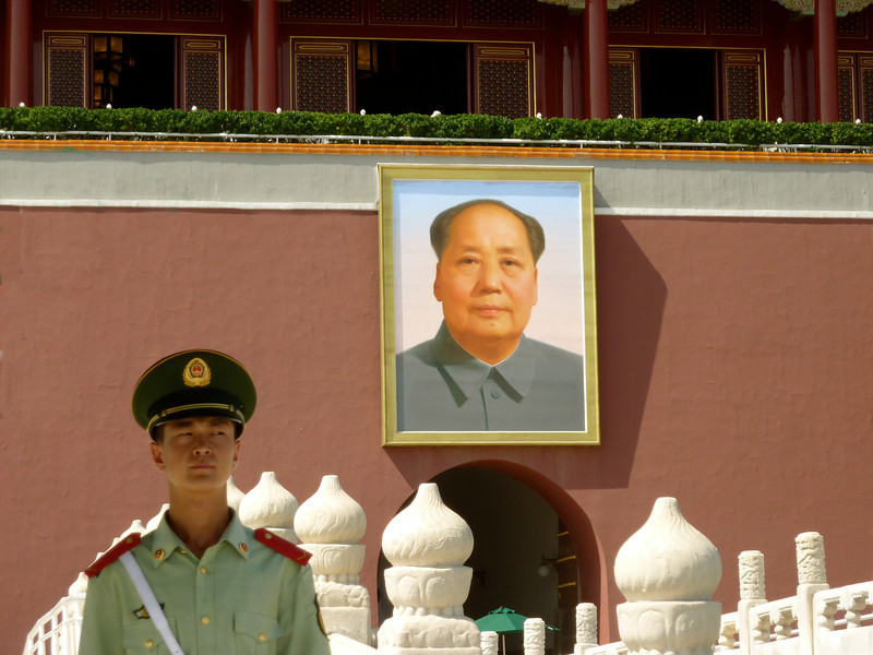 A guard outside of the south Meridian Gate entrance to the Forbidden City in Beijing.  Chairman Mao's portrait has an imposing presence.